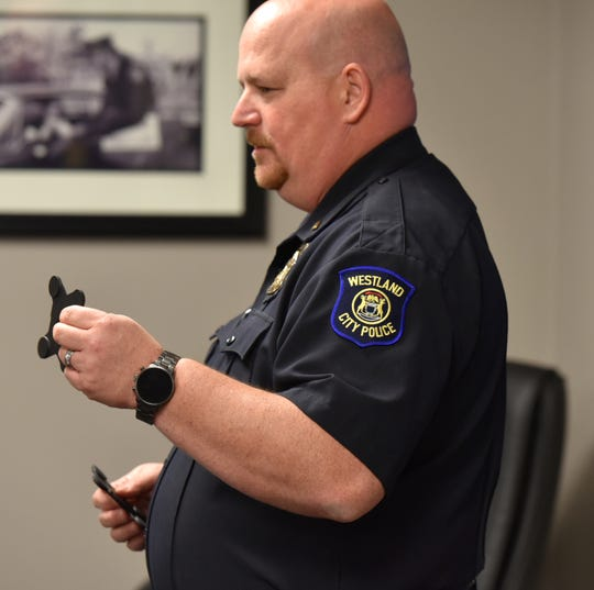 Westland Police Lt. Steve Bird instructed three new officers on how to attach their personal body cameras to their uniforms using two frame pieces held together with strong magnets.