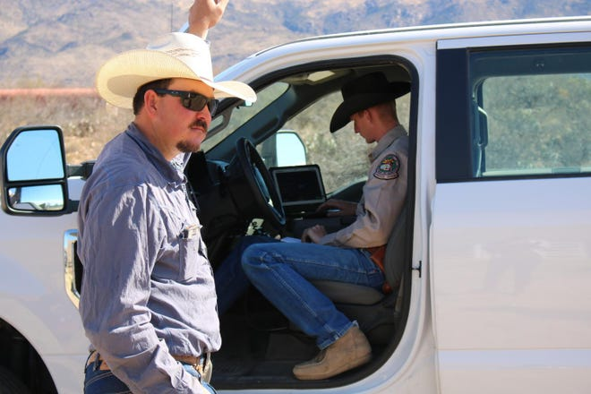 Ty Sorrells (left) goes out into rough country to round up stray or feral cows wandering around, while Livestock Officer Garrett Lacey takes a look at the found cows to make sure they weren't stolen.