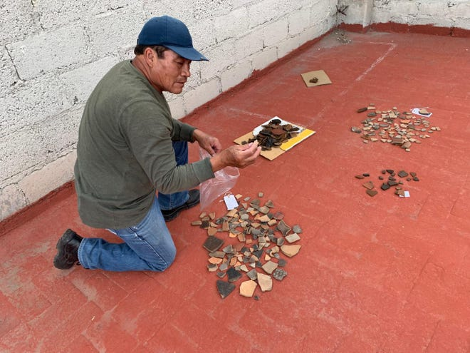 Amado Angel Llanos Reyes washes fragments of clay pottery excavated from Teotihuacan.
