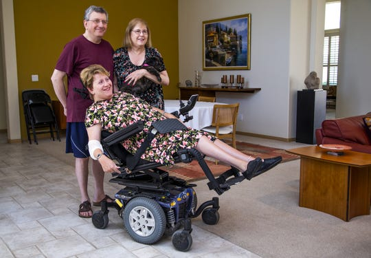 Michelle Murik uses a motorized wheelchair full-time and used to rely on Dial-A-Ride to get to her job. Murik, who has cerebral palsy, now has to depend on another service called RideChoice. She waits at home for her ride to work on Sept. 20, 2019. Her father, Sam Murik, and mother, Aleese, wait with her.