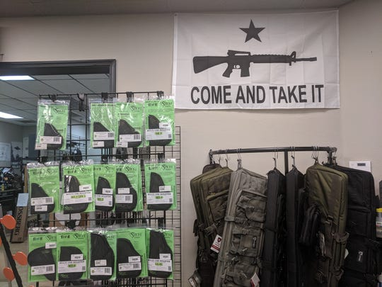 "A flag that reads, ""Come and take it"" below an image of an assault rifle hangs in Alpha Dog Firearms on Sept. 19, 2019.  Co-owner Matt Boggs said he thinks a belief in the Second Amendment ""supersedes"" any political affiliation."