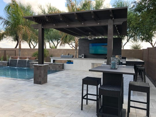 Travertine borders the pool and barbecue space.
