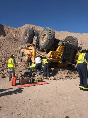 Mesa Fire & Medical rescue crews work to extricate the driver of a dump truck that overturned near Longbow and Higley roads Thursday.