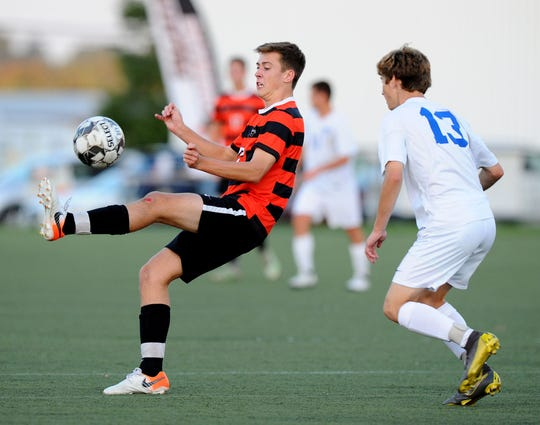 Palmyra's Alec Haldeman (12) tries to control the ball in-front of Lower Dauphin's Casey Ahern (13) during first half action.  Photo Jeff Ruppenthal