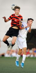 Joshua Mark (8) of Palmyra goes up to head the ball with Lower Dauphin's Josh Koteles (9) during first half action.