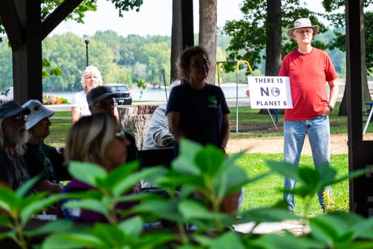 Richard Cannon, right, of Lexington, holds a sign as she listens to a performance by Port Huron musician Alex Shier in Pine Grove Park Friday, Sept. 20, 2019, during a rally as part of Global Climate Strike.
