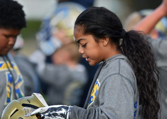 Taua Puloka, 11, gets ready to put her helmet on during practice. Puloka is the only girl in the team and the quarterback for Raiders in the The Sierra Youth Football League.
