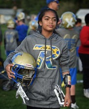 Taua Puloka, 11, stands ready to play during practice. Puloka is the only girl in the team and the quarterback for Raiders in the The Sierra Youth Football League.