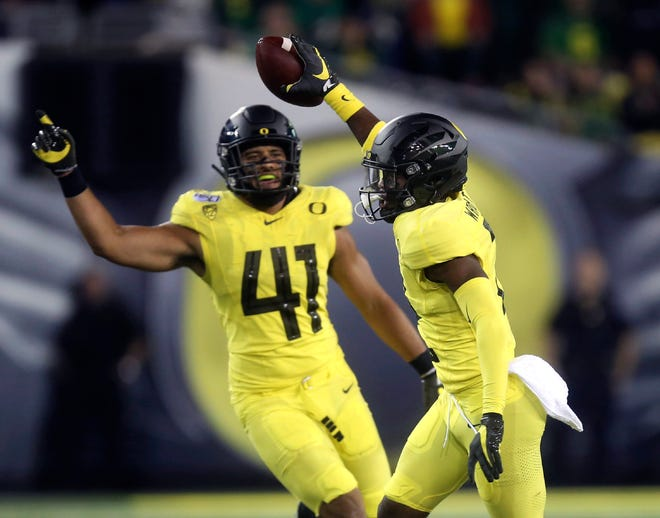 Oregon linebacker Isaac Slade-Matautia (41), here celebrating an interception by Mykael Wright in last year's home win over Montana, is trying to fill the leadership void in the middle of the defense left by Troy Dye.