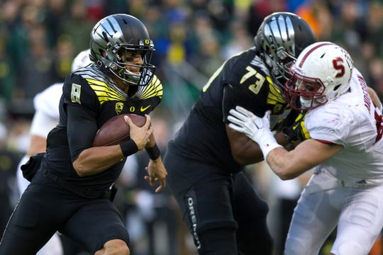 Nov 1, 2014; Eugene, OR, USA; Oregon Ducks offensive lineman Tyrell Crosby (73) blocks Stanford Cardinal linebacker Kevin Anderson (48) as Oregon quarterback Marcus Mariota (8) runs the ball for a first down at Autzen Stadium. Mandatory Credit: Scott Olmos-USA TODAY Sports