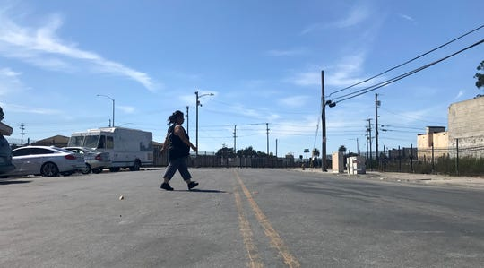 A woman crosses the street in Salinas's Chinatown where tents of people experiencing homelessness covered the sidewalk and edged into the street. Sept. 13, 2019.