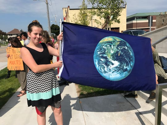 Cordelia Wensauer-Hofslund, a 14-year-old student at George D. Warriner High School holds a flag during a rally outside of Sheboygan City Hall Friday, Sept. 20, 2019. The rally was part of the Global Climate Strike.