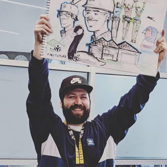 Mikey Martinez, from Comic Book Genie, holds up a drawing he made for the Habitat for Humanity TV spot.