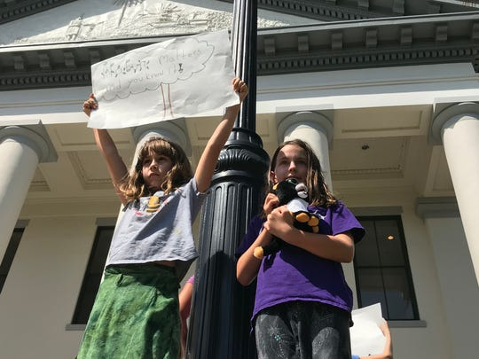 "Two children stood on the steps of Tallahassee's Old Capitol building Friday, September 20, 2019 to participate in the international ""Climate Strike."" Her sign reads, ""Nature matters and you know it!"""