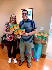 Joy Puerta, left, and Bolivar Gomez drop off heaps of markers collected by employees of the Martin County Commission for the United Way of Martin County Tools for Success initiative.