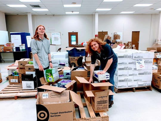 Martin County High School students Alex and Dylan Truver sort supplies for Tools for Success.