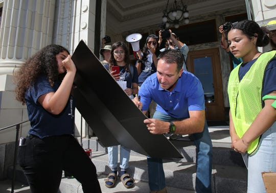 Ventura Mayor Matt LaVere signs a poster board in front of City Hall Friday. The board was signed by hundreds of climate activists who participated in Friday's Global Climate Strike in Ventura.