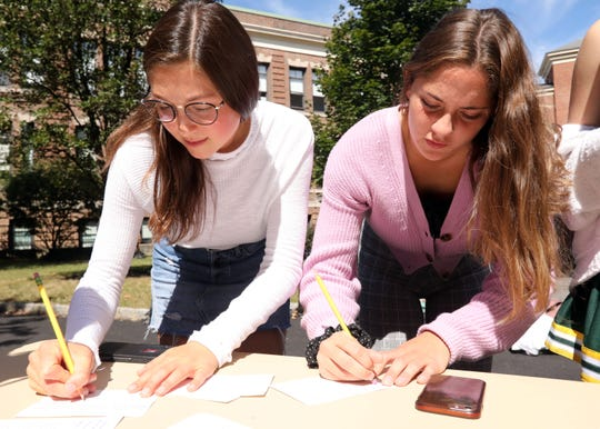 Seniors Juliana Ochacher, left, and Clara Lima write letters to local representatives at a climate change rally at Hastings High School during a Global Climate Strike Sept. 20, 2019.