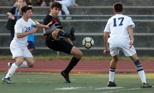 Rye's Connor Camacho (33) tries to keep the ball away from Byram Hills' Ross Eagle (29) and David Pereira (17) during boys soccer game at Rye High School Sept.19, 2019. Byram Hills defeats Rye 1-0.