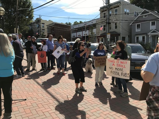 Protesters arrive for a rally against climate change outside Irvington Village Hall on Friday.