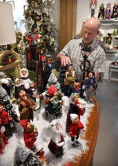 A display of carolers is set up by John Beer, who co-owns the Encore store with his wife, Cheryl Beer, formerly of The Last Straw.