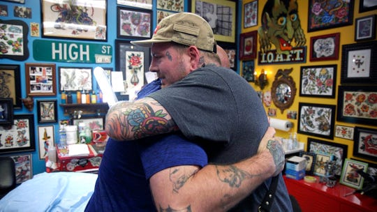 Zanesville tattoo artist Billy White hugs John Lemaster after covering up his tattoo of a Klansman on his back.