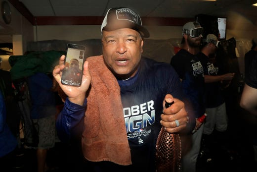 Los Angeles Dodgers coach Dave Roberts holds a cell phone during a video conference with injured player Max Muncy during a locker room celebration after the Dodgers defeated the Baltimore Orioles 7-3 during a baseball game on Tuesday. , September 10, 2019, Baltimore. The Dodgers have won the NL West title. (AP Photo / Julio Cortez) ORG XMIT: BAB20