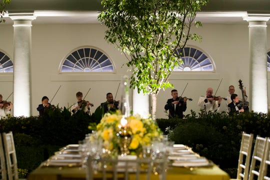 A table is set as a military band plays during a media preview for the State Dinner with President Donald Trump and Australian Prime Minister Scott Morrison in the Rose Garden of the White House, Thursday, Sept. 19, 2019, in Washington.