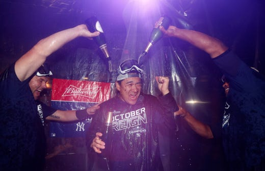 September 19: Yankees pitcher Masahiro Tanaka is bathed in champagne after New York's victory over the Orioles.