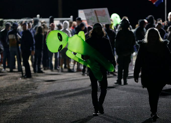 """A mans holds an inflatable alien at an entrance to the Nevada Test and Training Range near Area 51 Friday, Sept. 20, 2019, near Rachel, Nev. People gathered at the gate inspired by the """"Storm Area 51"""" internet hoax."""