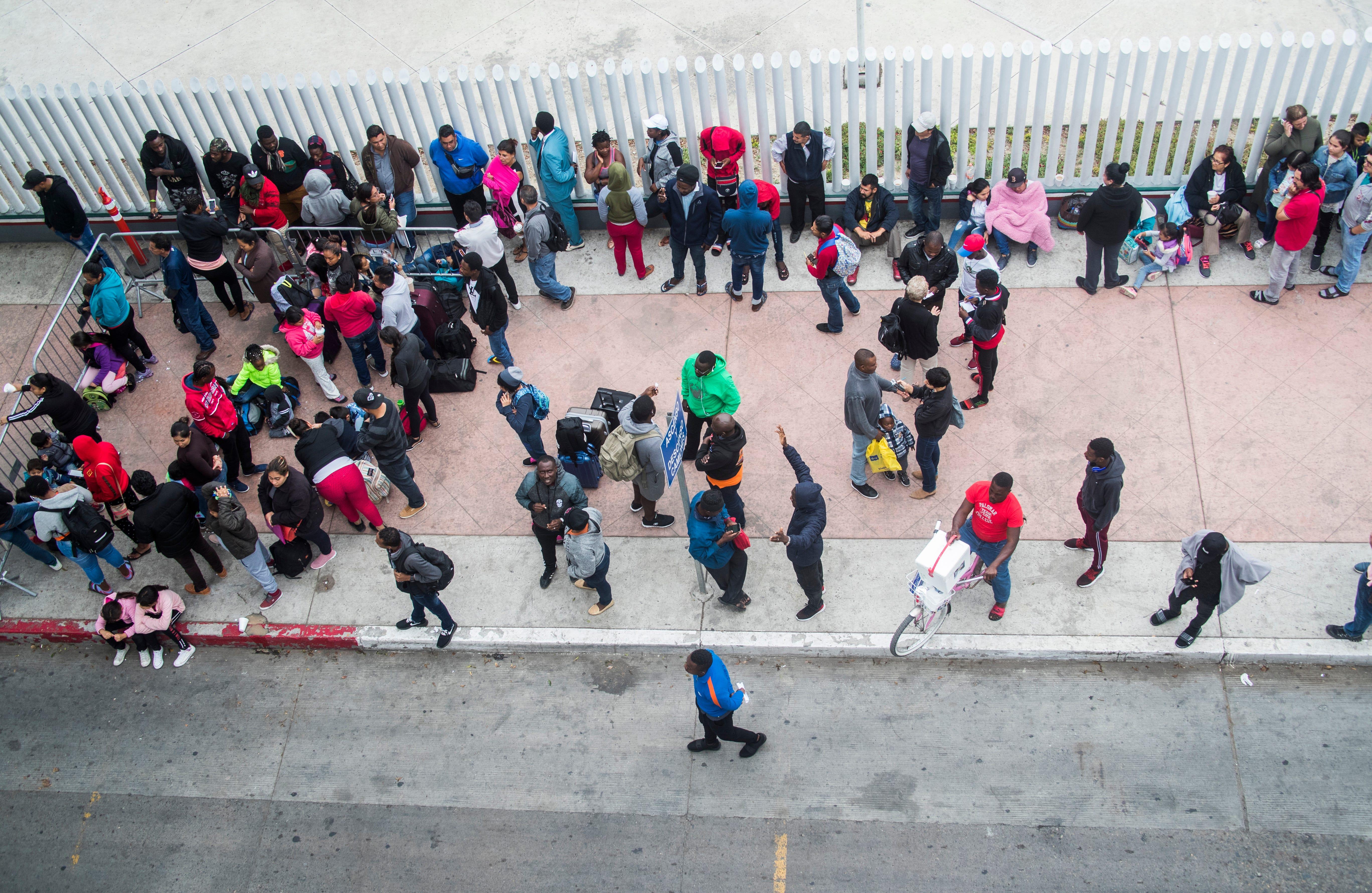 TIJUANA, México – Cientos de migrantes pasan por el ritual diario de visitar el puerto de entrada de El Chaparral a ver qué nombres fueron llamados de la lista de espera para introducir peticiones de asilo en los Estados Unidos. Los migrantes frecuentemente tienen que esperar semanas antes de ser llamados.