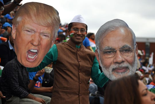 An India fan holds up over-sized portraits of US President Donald Trump and Indian PM, Narendra Modi in the crowd during the 2019 Cricket World Cup first semi-final between India and New Zealand at Old Trafford in Manchester, northwest England, on July 9, 2019.