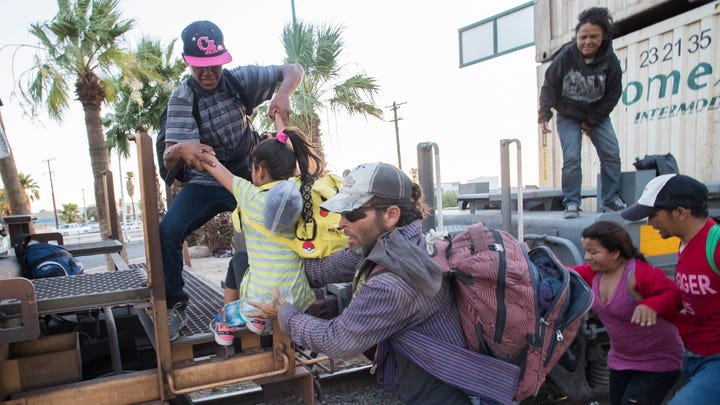 A child boards a moving train with the help of other migrants. The child was helped by adults in the group as her father and mother assisted her two younger siblings. The migrants were headed south after they were returned to Mexico by U.S. officials when they sought asylum.