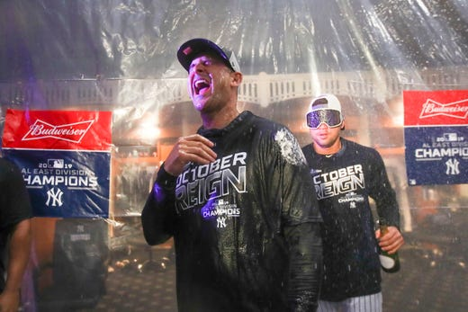 Players throw champagne at Yankees manager Aaron Boone.