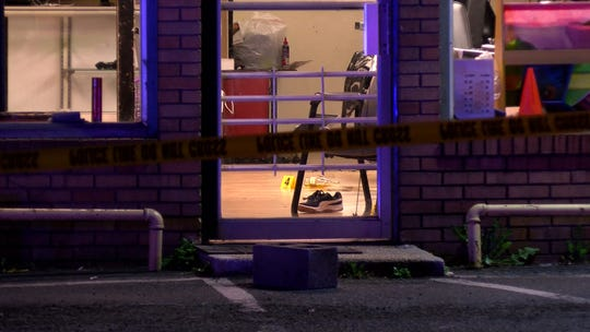 A sneaker and a police evidence marker are seen through the glass door of the R-NU Barbershop at 1030 Old Corlies Avenue in Neptune on Friday night, after two people were shot inside the business on this date, Sept. 20, 2019.