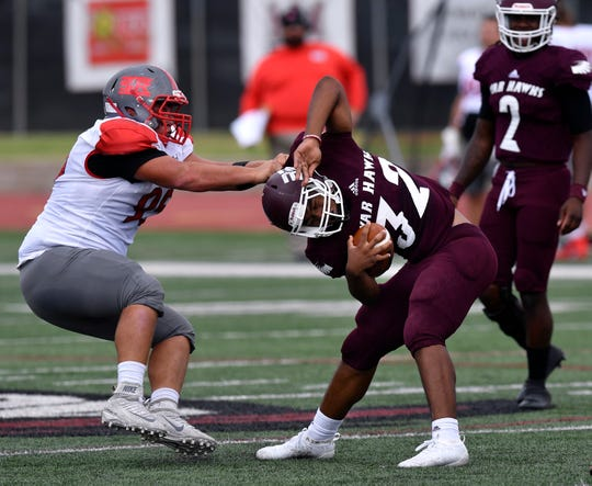 Sul Ross defensive lineman Marcus Luna attempts to bring down McMurry running back Dee Robinson by nearly pulling off his jersey during their game Sept. 21 at McMurry. The War Hawks lost, and are 0-4 on the season.
