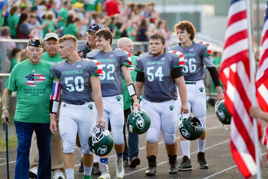 Members of the Pennfield varsity football team walk out with military veterans before kickoff as part of Military Appreciation Night on Friday, Sept. 20, 2019.