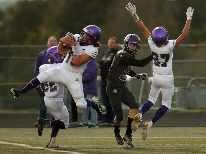 Sequim's Taig Walker (left) intercepts a pass intended for North Kitsap's Erich Burchill (center) during the first half of their game in Poulsbo on Friday, September 20, 2019. The play was called back due to pass interference against Sequim.