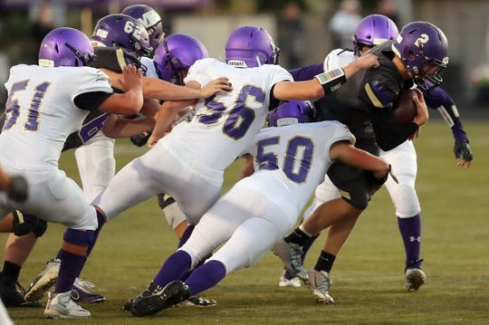 Sequim defenders Lane Mote (51),  Mitchell Horton (56) and Isaiah Cowan (50) try to bring down North Kitsap quarterback Colton Bower (2) during the first half of their game in Poulsbo on Friday, September 20, 2019