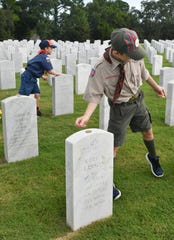 Josh and Sam Moinot, ages 9 and 7, place coins on the markers of veterans at Cape Canaveral Memorial Cemetery in Scottsmoor Saturday morning. The coins were placed in memory of every soldier who served in the military.