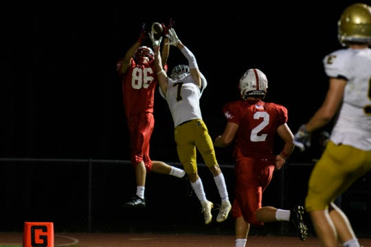 Rutland's Luke Ragosta (86) leaps over Essex's Luke Meunier (7) to catch the ball for a touchdown during the high school football game between the Rutland Raiders and the Essex Hornets at Essex High School on Friday night September 20, 2019 in Essex, Vermont.