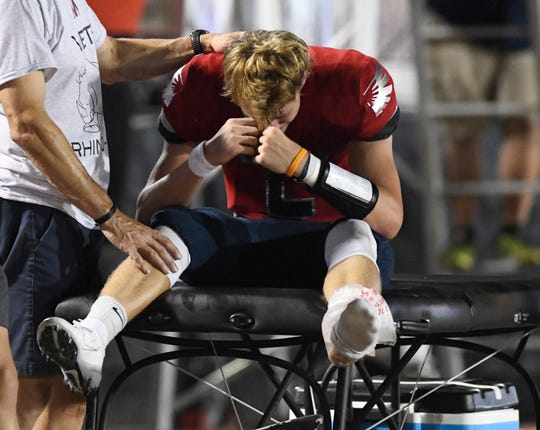Veterans Memorial's quarterback Carter Senterfitt is comforted on the sidelines by his father Jay Senterfitt after suffering an injury during the game against Flour Bluff, Friday, Sept. 20, 2019, at Cabaniss Stadium. Senterfitt became injured late in the first quarter.