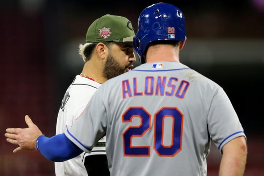 Cincinnati Reds third baseman Eugenio Suarez (7), left, who has 48 home runs, and New York Mets first baseman Pete Alonso (20), right, who leads the league with 50 home runs, talk in the ninth inning of an MLB baseball game, Friday, Sept. 20, 2019, at Great American Ball Park in Cincinnati.