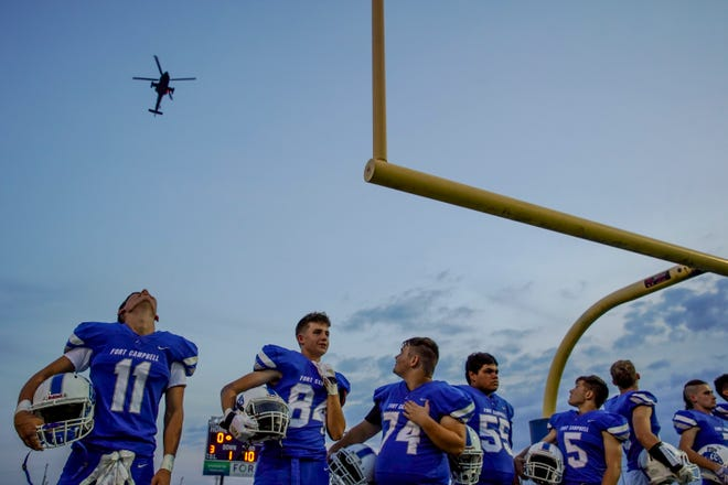 Fort Campbell players look back and over their shoulders at a helicopter flying over during the national anthem in a KHSAA game between the Fort Campbell Falcons and Fort Knox Eagles at Fort Campbell High School Fryar Stadium in Fort Campbell, KY., on Friday, Sept. 20, 2019.