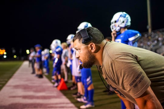 Fort Campbell's head coach Josh Robins leans in and watches his players from the sidelines in a KHSAA game between the Fort Campbell Falcons and Fort Knox Eagles at Fort Campbell High School Fryar Stadium in Fort Campbell, KY., on Friday, Sept. 20, 2019.