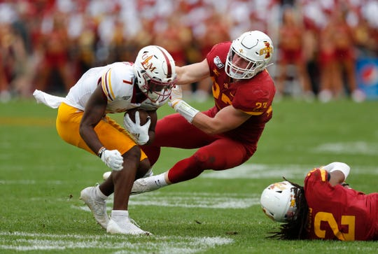 Iowa State linebacker Mike Rose, center, looks to pull down Louisiana-Monroe wide receiver Zach Jackson, left, during the first half of an NCAA college football game, Wednesday, Aug. 14, 2019, in Ames.