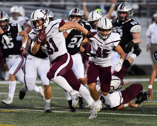 Dowling's Teagan Johnson (31) blows through the line for a touchdown on Friday, Sept. 20, 2019 during a game between the Ankeny Centennial Jaguars and the Dowling Catholic Maroons.