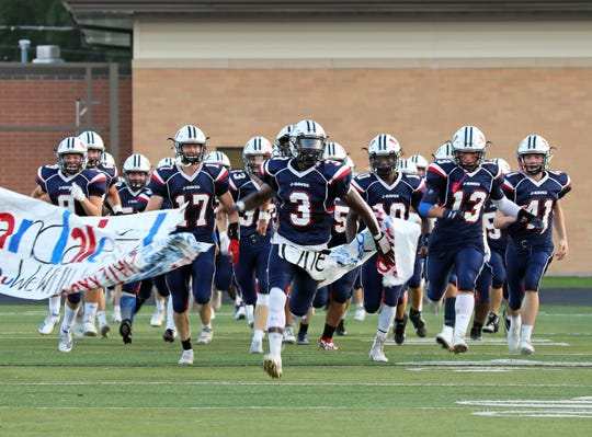 Urbandale senior running back and Northern Illinois commit Harrison Waylee (3) breaks through the banner before the Linn-Mar Lions battle against the Urbandale J-Hawks during the Class 4A game on Friday, September 20, 2019 at Frerichs Field in Urbandale.