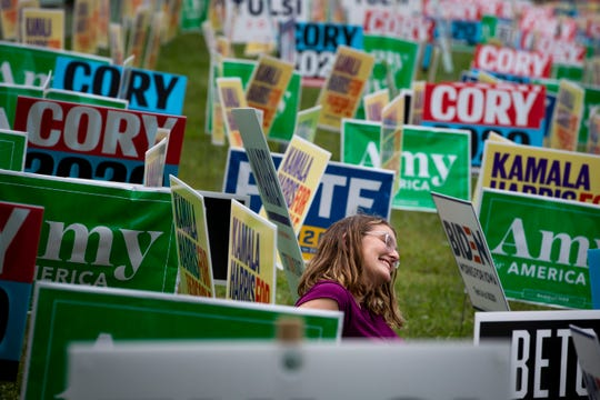 Ella Field of Illinois takes a photo amount the yard signs lining a hill during the Polk County Democrats Steak Fry in Water Works Park on Saturday, Sept. 21, 2019 in Des Moines.