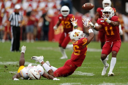 Iowa State defensive back Lawrence White, right, intercepts a pass intend for Louisiana-Monroe wide receiver Zach Jackson, left, after Iowa State defensive back Anthony Johnson, center, tipped the ball during the first half of an NCAA college football game, Wednesday, Aug. 14, 2019, in Ames.